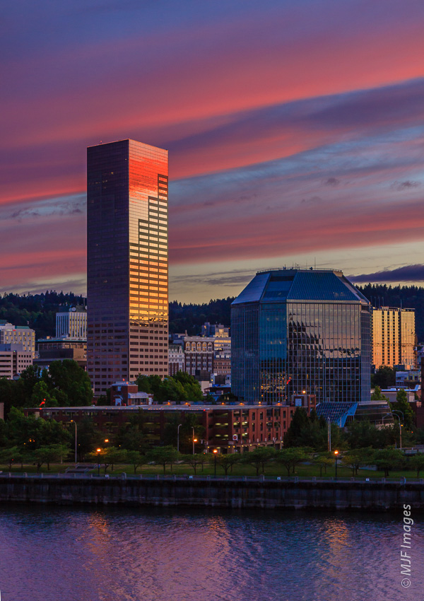 A Portland, Oregon cityscape is improved by the sky's beautiful light being reflected off the skyscraper.