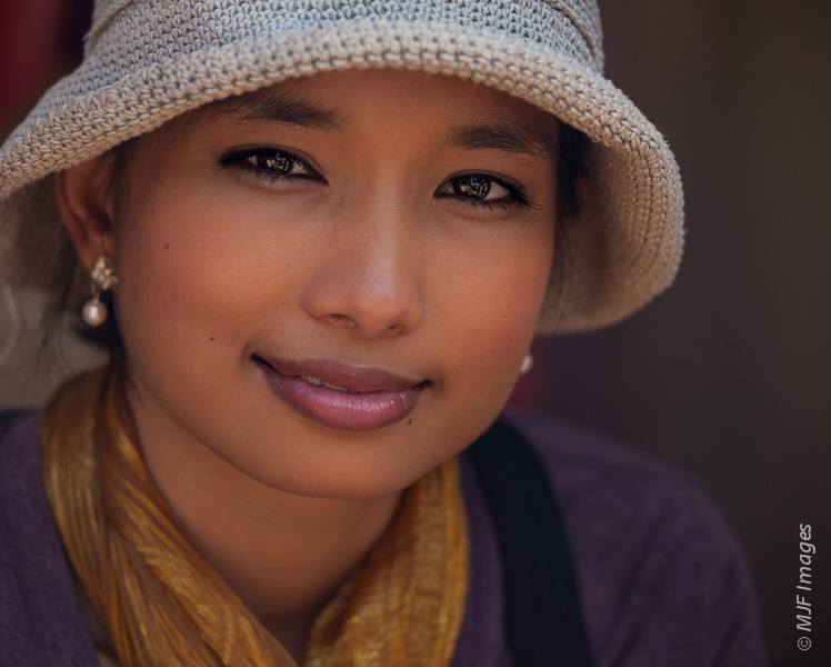 This pretty young woman's eyes act as mirrors in this image from Cambodia, creating good catchlights.  But my own reflection is almost too obvious.