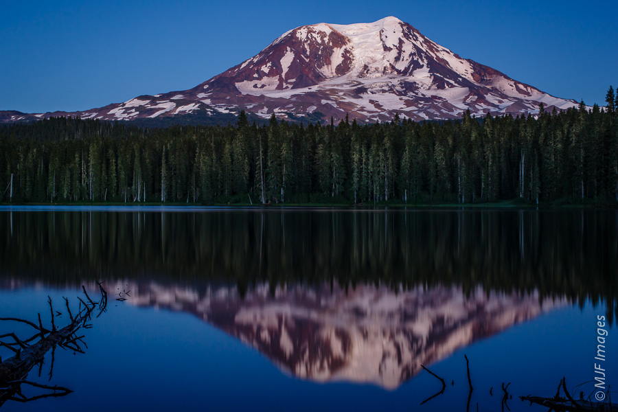 Mount Adams, Washington is reflected in Tahklakh Lake at blue hour.