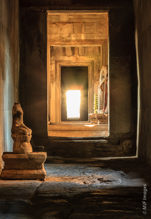 A lonely corridor faces the sinking sun at Angkor Wat in Cambodia.  Nested rectangles are featured.