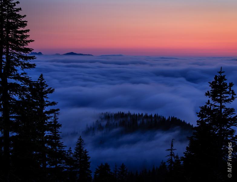Fog fills the valleys beneath Mount Rainier as evening arrives.