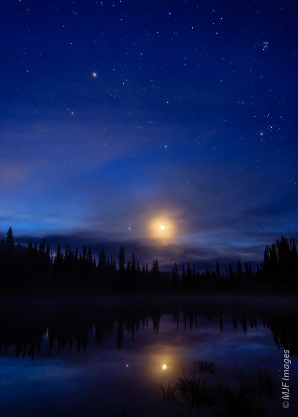 Before dawn at Mt Rainier National Park, the moon rises over Reflection Lake.