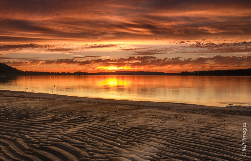 An empty beach along the lower Columbia River in Oregon glows with a colorful summer sunset.