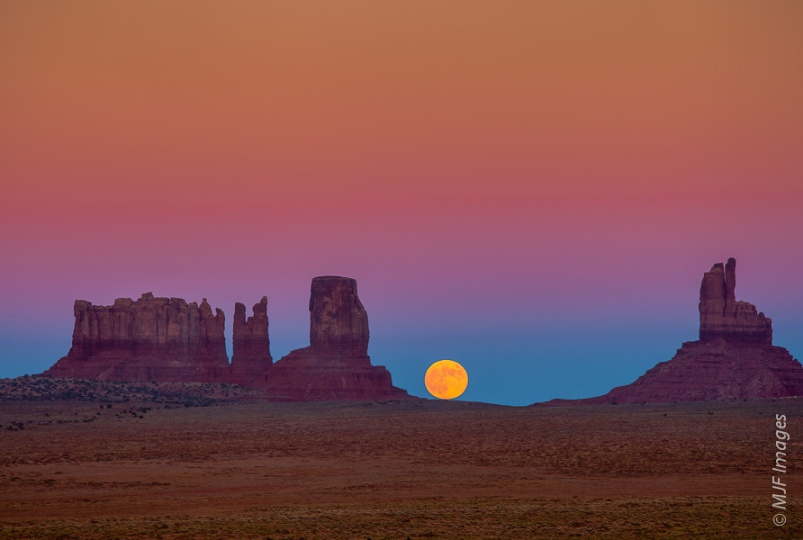The perfect circle of the rising moon contrasts with the unusual shapes that make Monument Valley in the American Southwest so famous.
