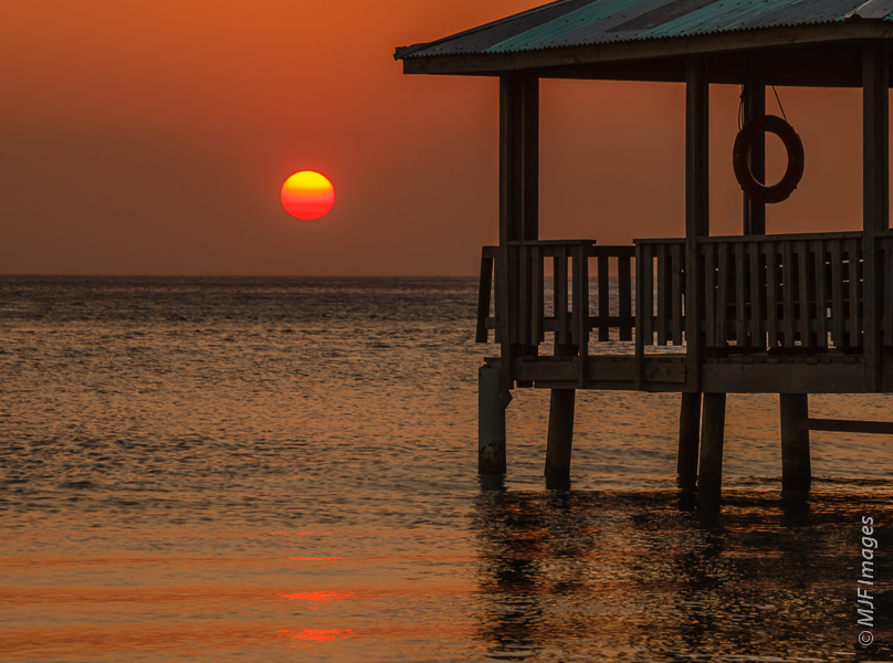 I was attracted to this covered pier on the island of Roatan in Honduras partly because of the lifesaver hung there.  It supports the circular shape of the setting sun.  Both circles are set off by the rectangular frame of the pier.
