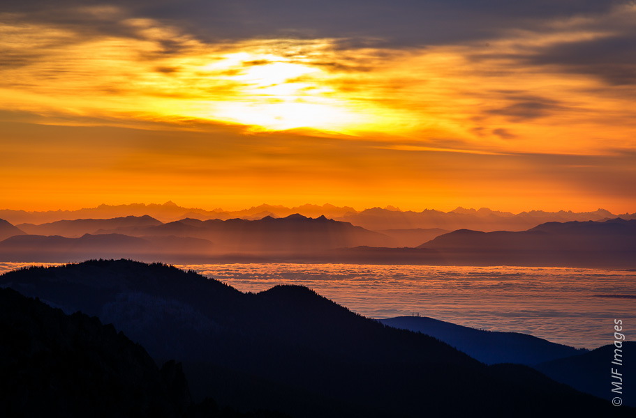 Light from the rising sun fills valleys of the North Cascades and reflects off low clouds covering the waters of Puget Sound in Washington.