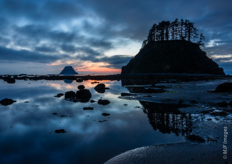 Dusk falls on the Olympic Coast in Washington.  Foreground elements are simple here, a combination of silhouetted rocks and subtly illuminated sand.