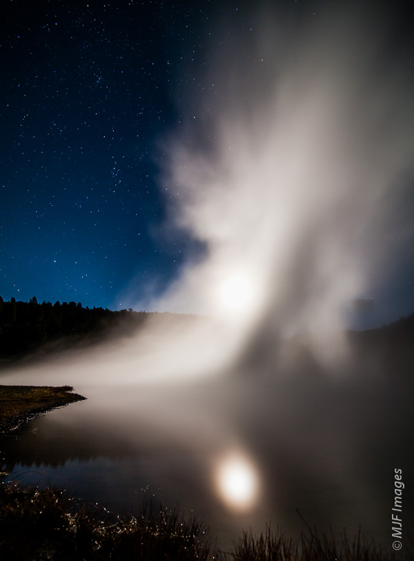 Here on a frigid night at Yellowstone National Park, the moon is reflected in a hot pool even though the steam obscures it's shape above.
