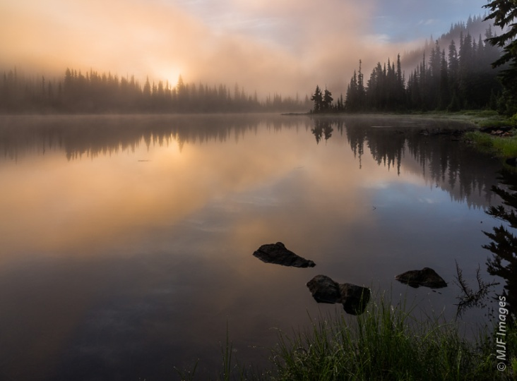 The sun struggles to break through the fog at sunrise on Reflection Lakes, Mount Rainier National Park.