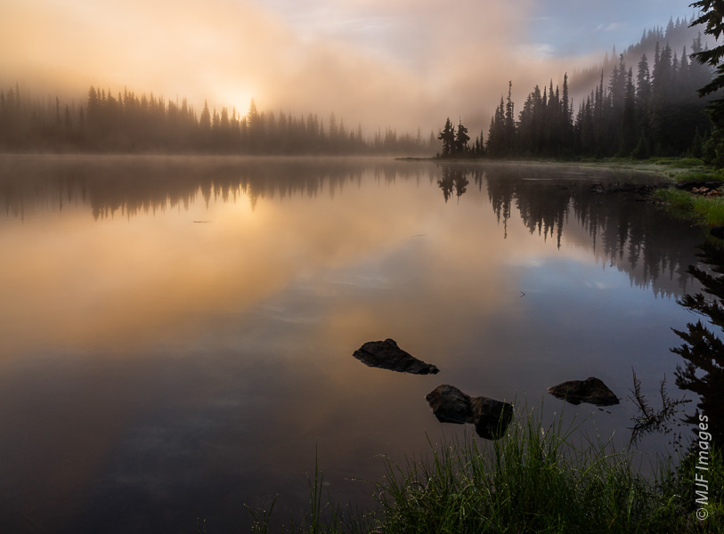The battle between the rising sun and thick fog at Reflection Lake on Mount Rainier turns in favor of the sun.