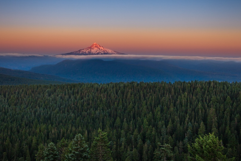 Mount Hood and its enveloping forest are highlighted in this image shot at 28 mm.  Most photographers would zoom in on the mountain to make it bigger, but I wanted to put equal emphasis on the surrounding forest.