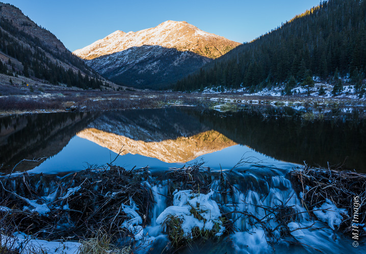 A large beaver pond reflects a high mountain in the Colorado Rockies.