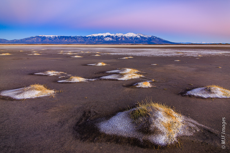 A dry lake bed just west of Colorado's Great Sand Dunes, the Sangre de Cristos Mountains in the background.