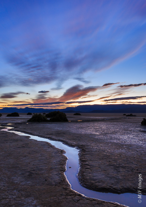 View out onto the Alvord Desert at dusk, where recent rains have left small pools and channels of water.