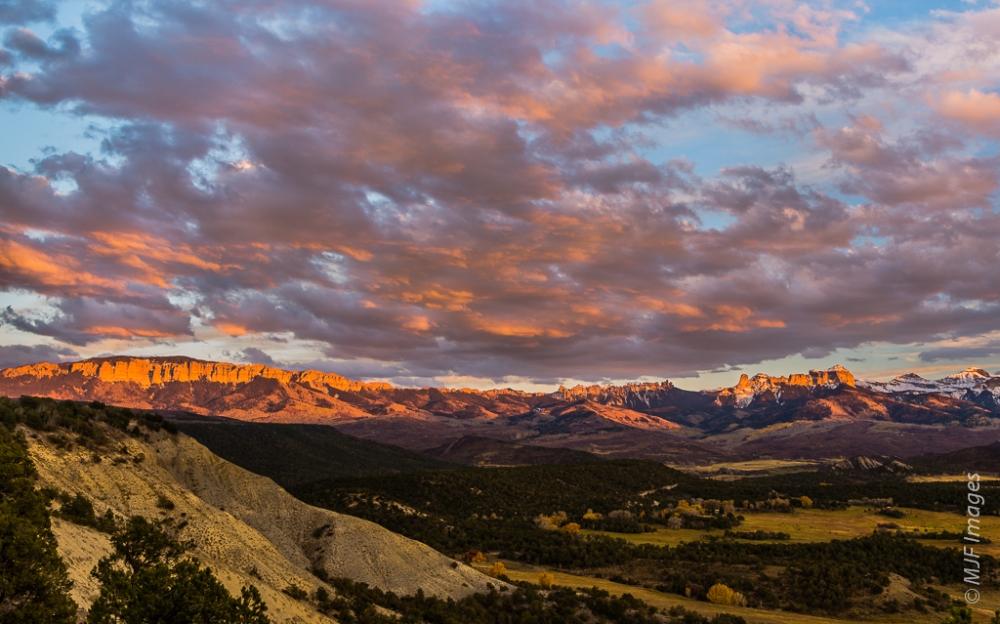 The setting sun's light brightens the peaks of the San Juan Mountains,  Colorado.