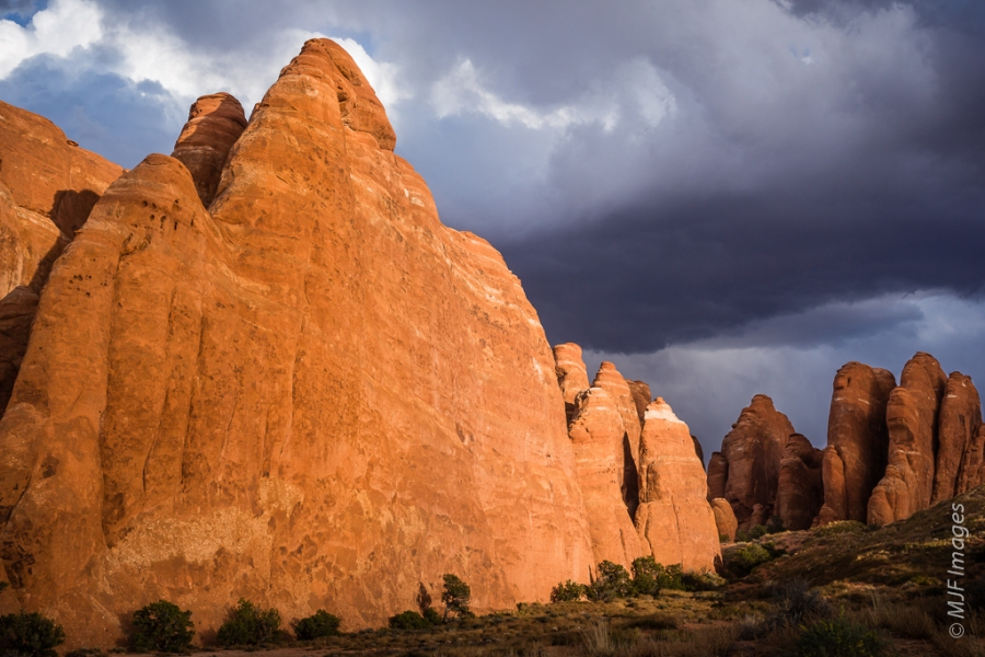 The rock monoliths and fins of Fiery Furnace in Arches National Park, Utah are bathed in late afternoon sunshine under a threatening sky.