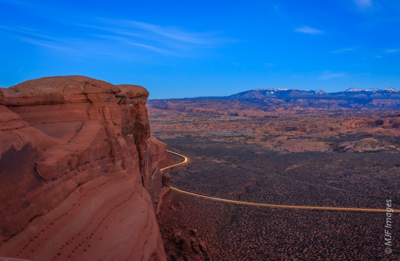 On a different hike in Arches National Park, I decided to capture what it's like to still be on the edge as darkness falls.  Car headlights trace the park road.