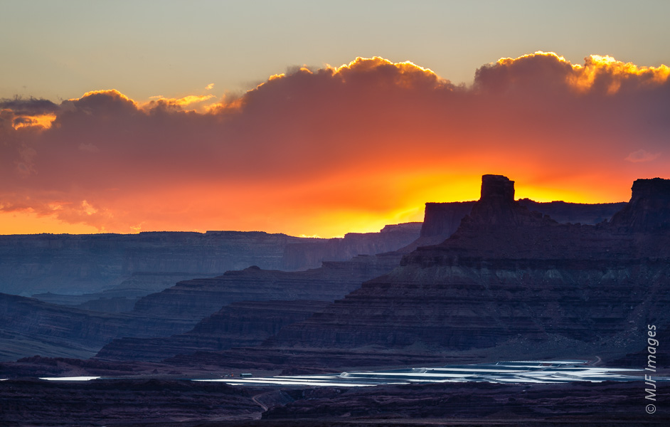 The settling ponds for the potash mine along the Colorado River near Moab are set off against a colorful sunset sky.