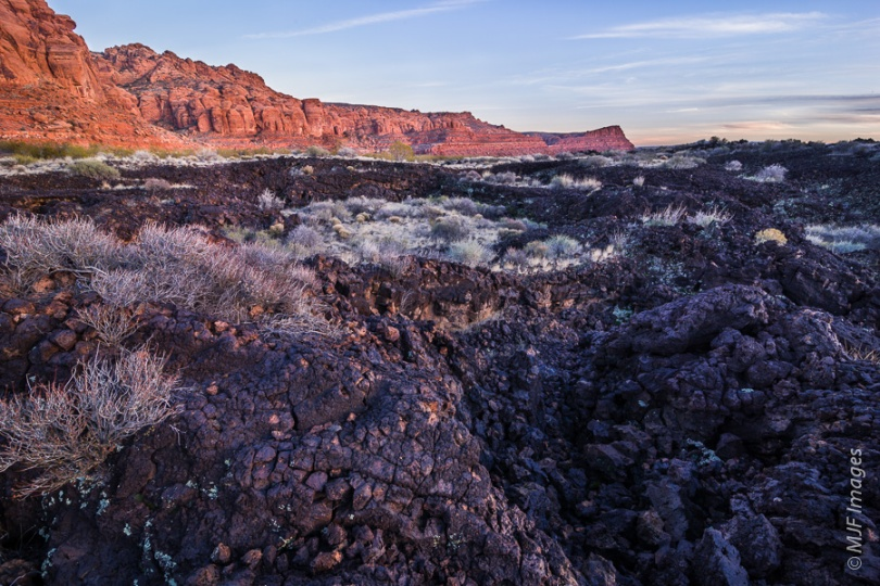 Black basalt (lava rock) occupies the canyon floors at Snow Canyon, Utah.