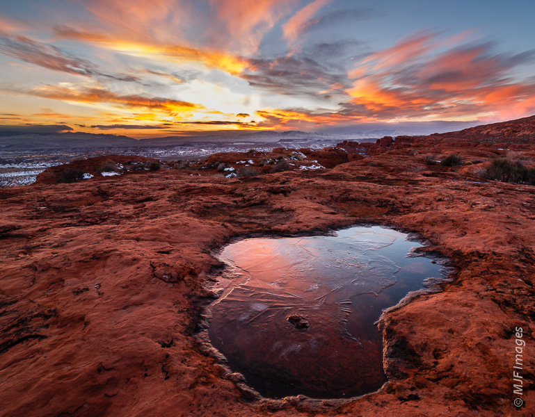A frozen water-pocket reflects the dusk sky in the red-rock country of southeastern Utah.