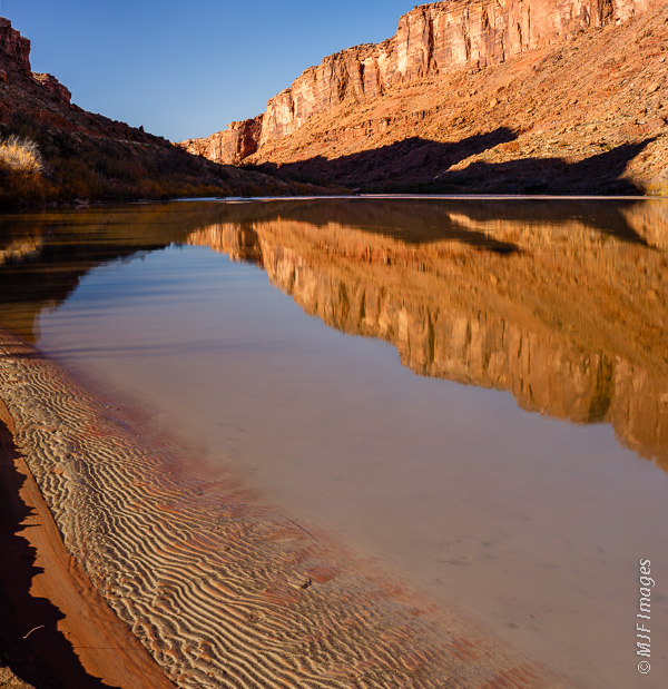 The Colorado River is smooth and quiet as it flows past the sandstone cliffs near Moab, Utah.