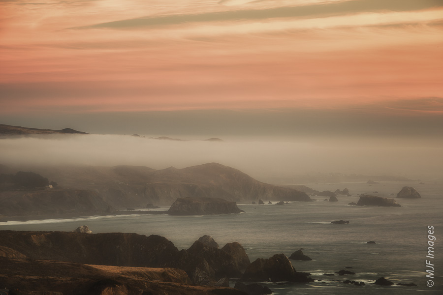 The light at dusk is subdued by fog and spray from the Pacific in this view south along the Sonoma Coast, California.