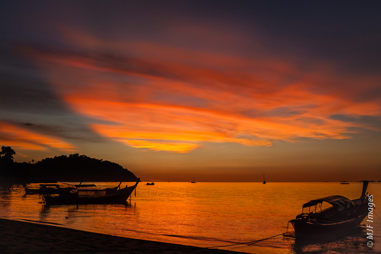 Traditional fishing boats are secured in a placid little bay on the island of Koh Lipe in the Andamon Sea off the coast of Thailand.