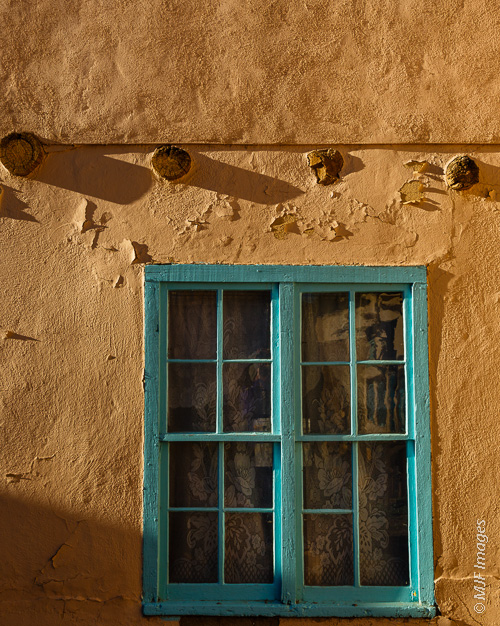 The adobe construction of this historic home in Taos, New Mexico is apparent in this image.