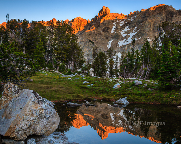 The Grand Tetons in Wyoming are reflected in a high alpine tarn.