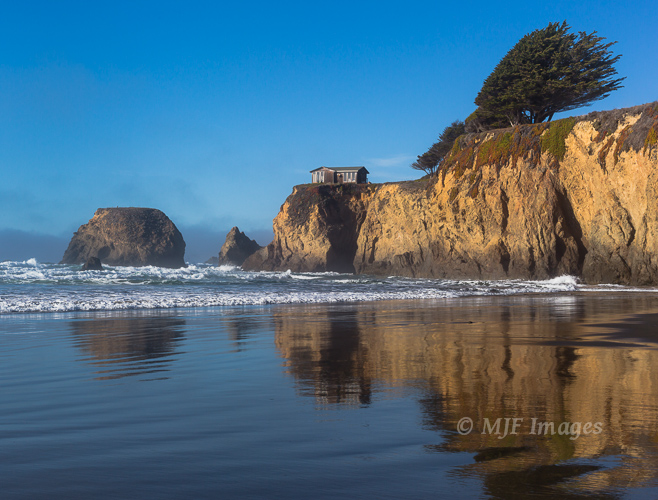 This house and the Mendocino Coast (California) headland it sits on are reflected beautifully off wet sand.