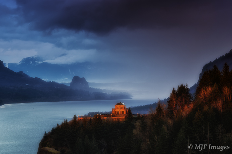 Low clouds and fog filling the Columbia River Gorge help add impact to this image of the Vista House catching day's last light.