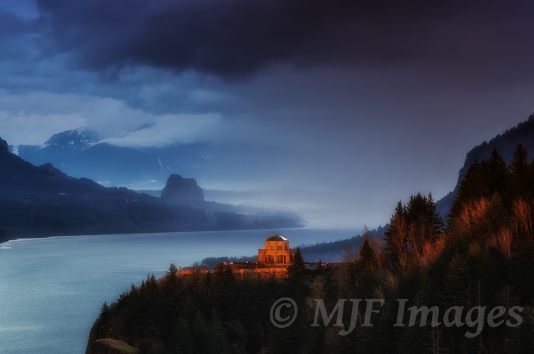 At sunset, mist and fog fill Oregon's Columbia River Gorge behind Vista House.