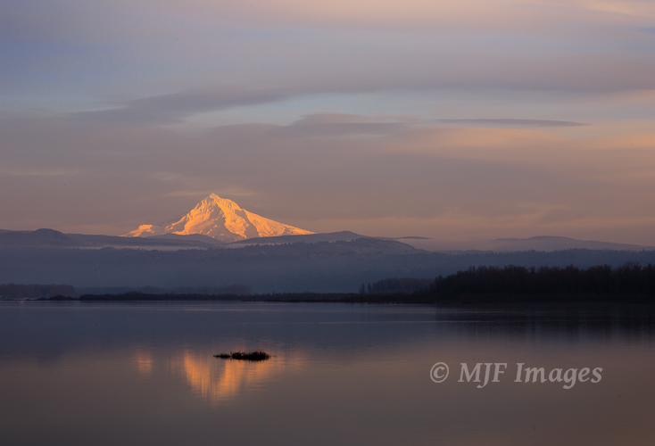 The setting sun lights up Mount Hood as it watches over the Columbia River.
