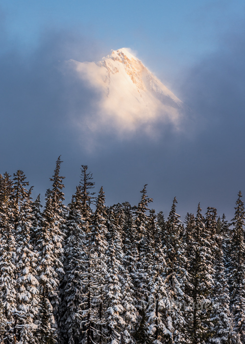 Mount Hood peeks out from low clouds on a frosty morning after overnight snowfall.