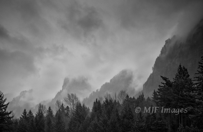 This black and white image of a stormy Columbia River Gorge is mostly shadow and mid-tones, with modest contrast.