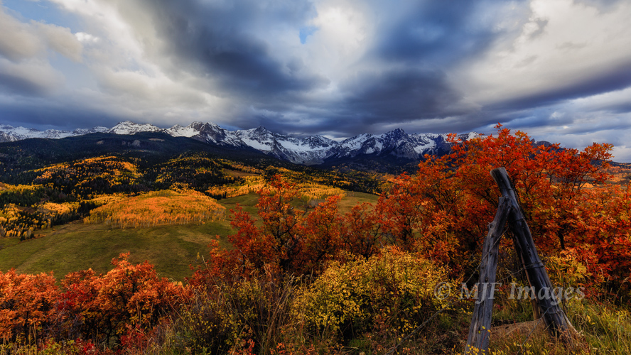 An old fence-line tops a ridge and Colorado's San Juan Mountains show off their autumn colors.