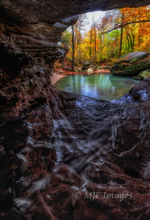 A stream running through a cave in the Ozarks drops into a pretty little pool.