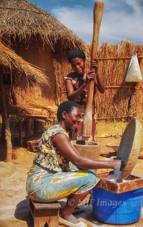 Two local women crack up while preparing casava in a small village above Lake Malawi.