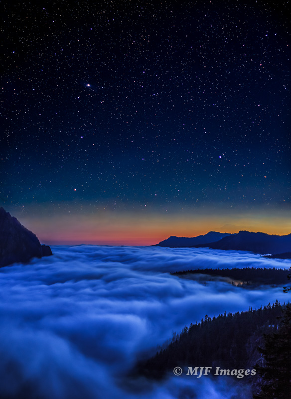 High up on Mt. Rainier, clouds filling the valley below helped to reveal the edge of night.