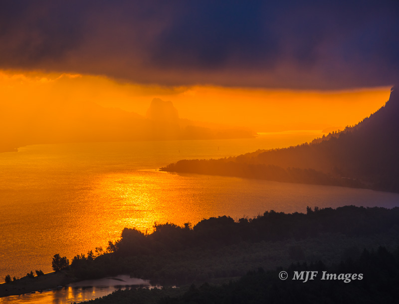 Beautiful light floods the Columbia River in Oregon at sunrise, and Beacon Rock (my subject) is almost lost as a result.