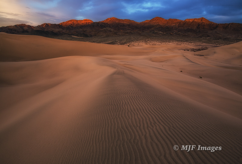 The Ibex Dunes lap up against a range of desert mountains.