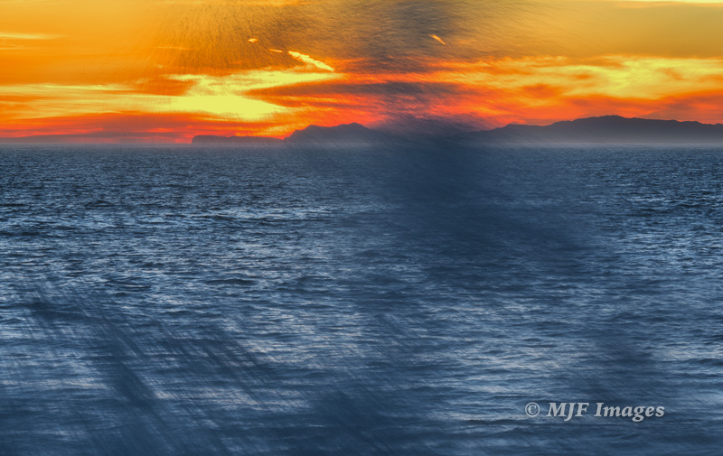 A California sunset with the Channel Islands and blowing sea-spray.