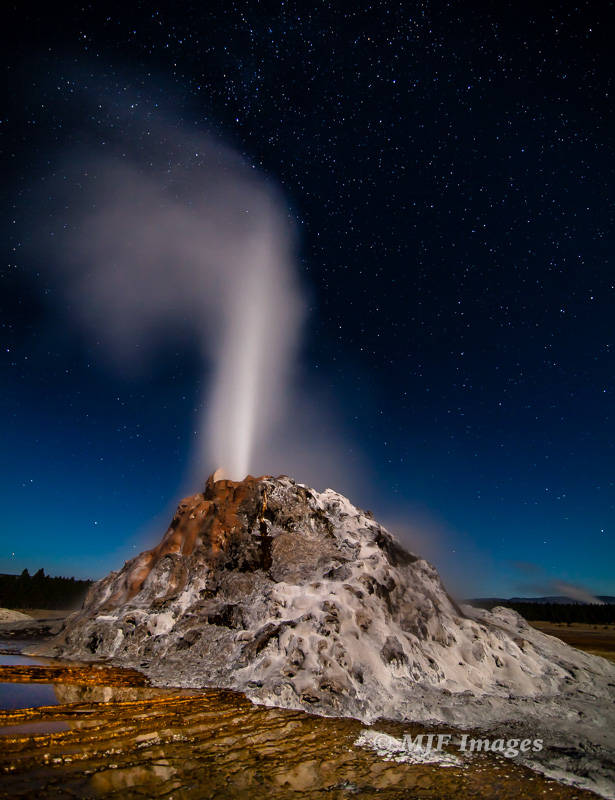 White Dome geyser erupts into a starry night.