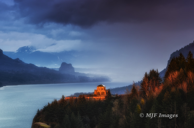 The classic view of Vista House and the Columbia River Gorge, Oregon in the light of a passing storm.