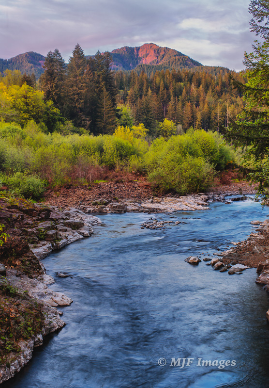 The Wilson River flows west from the rugged peaks of Oregon's Coast Range, including King's Mtn. visible in the distance.