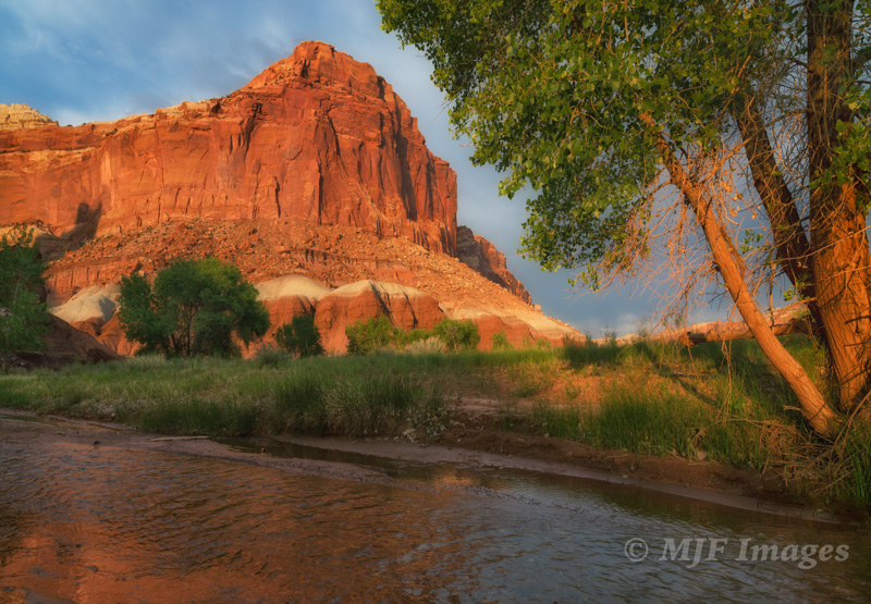 The setting sun highlights the walls of Capitol Reef, Utah, with the Fremont River flowing through it.