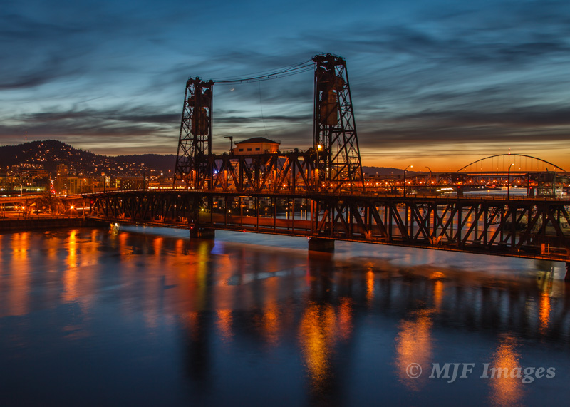 Portland, Oregon is a town of bridges, like the Steele Bridge here spanning the Willamette River at dusk with a crescent moon.