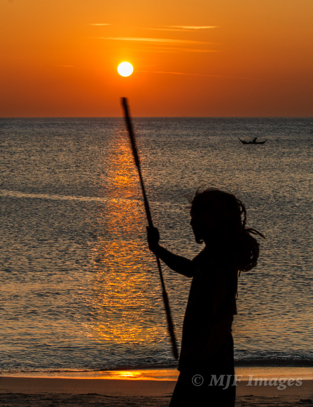 The sun sets on a southern Thailand beach as this fire-dancer practices for the evening performance.